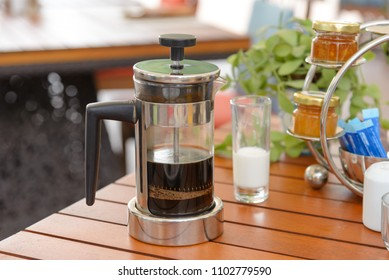Black coffee in French press coffee with milk on wooden table for breakfast