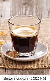 Black coffee in a glass with brown sugar crystals