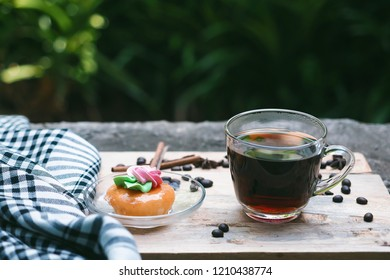 Black coffee in a glass cup has cakes in the dish. Put on wooden table In the garden there is space for text.