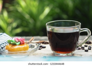 Black coffee in a glass cup has cakes in the dish. Put on wooden table In the garden there is space for text ,top view.