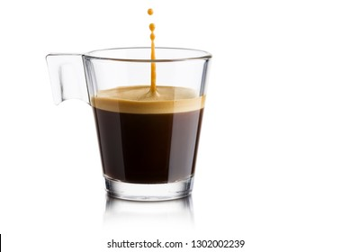 Black coffee in glass cup with jumping drop on white background