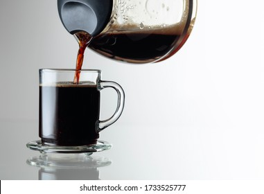Black coffee in a glass cup on a glass table. Coffee is poured from the coffee maker into a cup. Copy space.