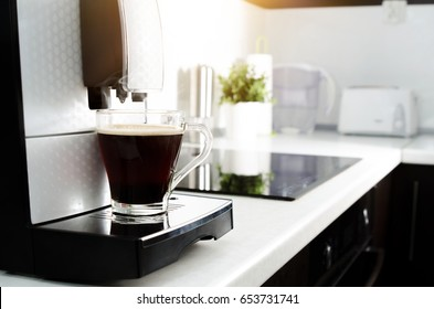 Black coffee in glass from coffee maker machine. coffee machine lungo kitchen glass hot italian concept