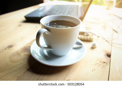 Black coffee in a glass placed on a wooden floor vintage style.
