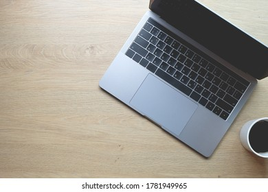 Black coffee with laptop computer on wooden table copy space