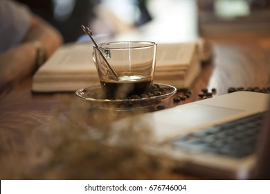 Black coffee and laptop on wooden table