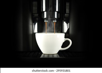 black coffee machine and white cup of coffee in dark space
