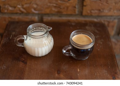Black coffee and milk on wooden table