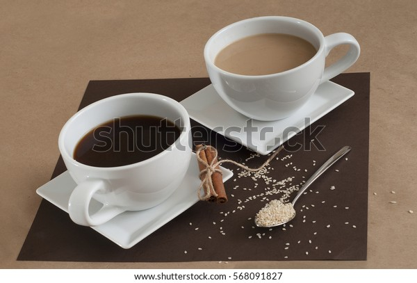 Black coffee and coffee with milk in white cups. Cinnamon and sesame.