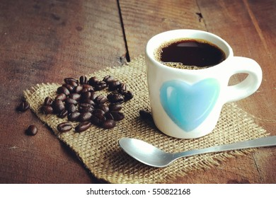 Black coffee, Morning coffee and roasted coffee beans on old wooden table and vintage background