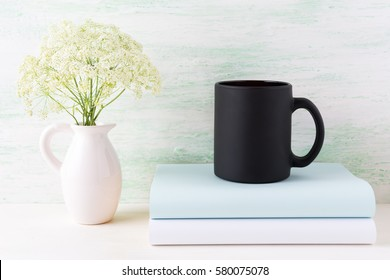 Black coffee mug mockup with books and tender white flowers. Empty mug mock up for brand promotion.
