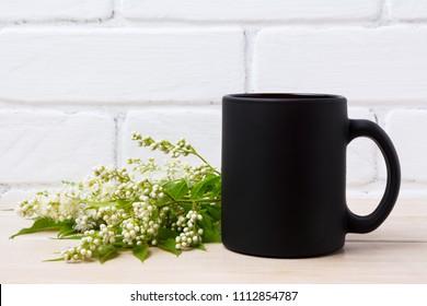 Black coffee mug mockup with Spiraea alba white Meadowsweet flowers. Empty mug mock up for brand promotion.