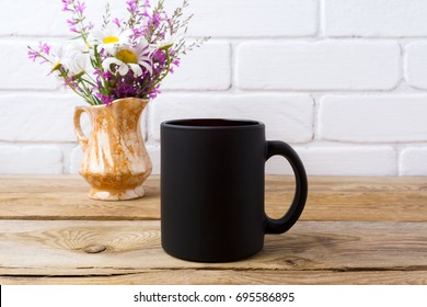 Black coffee mug mockup with white chamomile and purple field flowers in golden pitcher vase. Empty mug mock up for brand promotion.