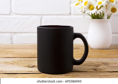 Black coffee mug mockup with white field chamomile bouquet in handmade rustic vase. Empty mug mock up for brand promotion.