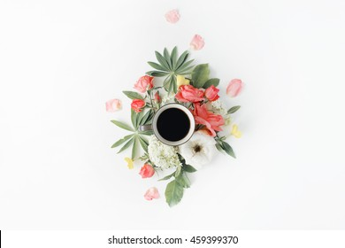 black coffee mug, pink roses and white hydrangea flowers bouquet on white background. flat lay, top view