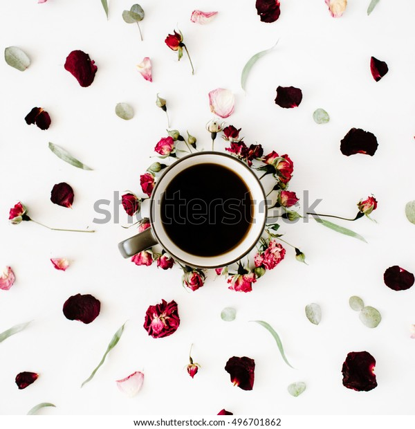 black coffee mug and red rose buds bouquet with eucalyptus on white background. flat lay, top view