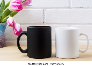 Black coffee mug and white cappuccino cup mockup with magenta pink tulip in the purple blue pitcher vase. Empty mug mock up for brand promotion.