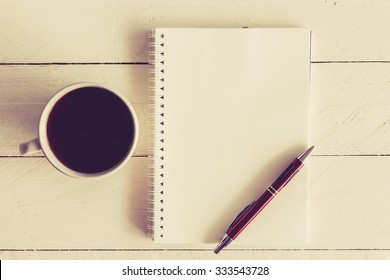 Black coffee with notebook and pen on wooden background - vintage tone