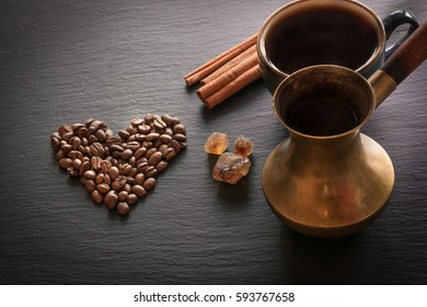 Black coffee in old copper cezve and cup and coffee beans on black slate as background with copy space.