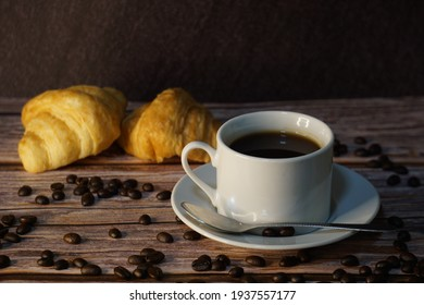 A black coffee on the table with croissant