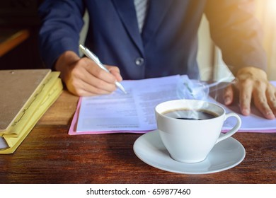 Black coffee on a wood table in the morning and a file with a male businessman signing a document at work.