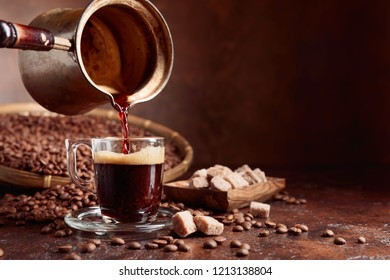 Black coffee is poured into a small glass cup from a copper coffee maker. Coffee beans and brown sugar pieces on a old table. Copy space.