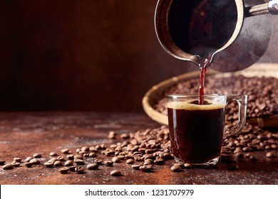Black coffee is poured into a small glass cup from a old copper coffee maker. Copy space.