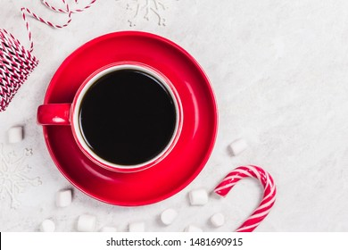Black coffee in red cup on white marble background, Christmas  ornaments. Top view, space for text.