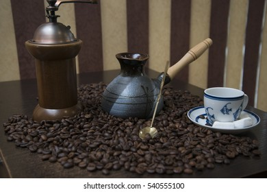 Black coffee scattered on the table. On the table are a coffee grinder Turka and cups.