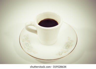 Black coffee in small coffe mug isolated. (Vintage Filtered)