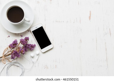 Black coffee with smartphone on white rustic wooden background