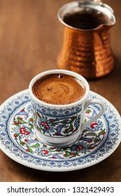 Black coffee in traditional Turkish cup with cezve on the background