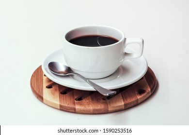 Black coffee in a white ceramic cup with saucer and spoon on the top of a round wooden placemat