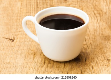 Black coffee in white ceramic cup on wooden table - studio shoot