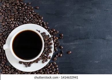 Black coffee in a white coffee cup and coffee beans placed on a black background. Top view