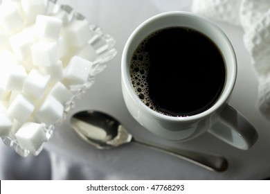 Black coffee in white cup with sugar cubes and spoon on white table cloth