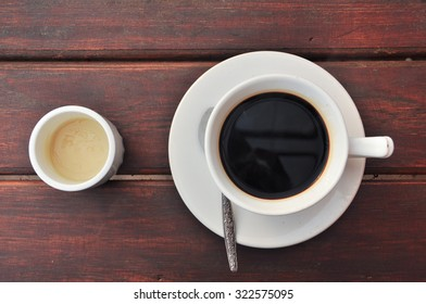 Black coffee in white cup and syrup