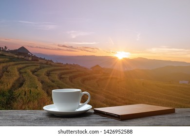 Black coffee in white cup and tablet on wooden table and the rice field background