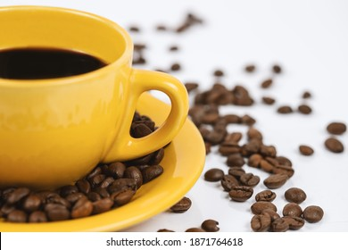 Black coffee in a yellow cup on a white background, surrounded with coffee beans.