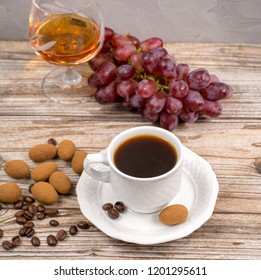 Black coffie and glass with brandy served with fresh grape and chocolate