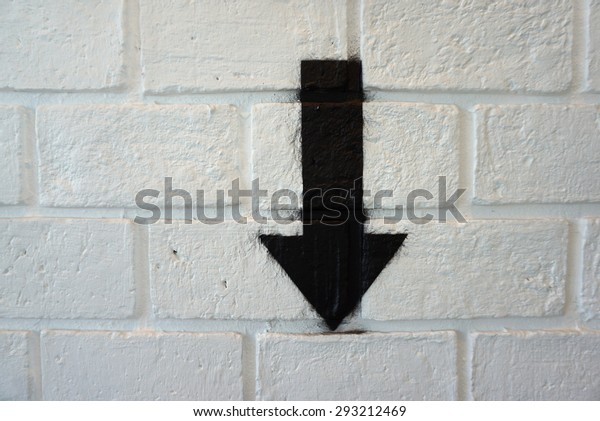 Black color down arrow sign on white brick wall