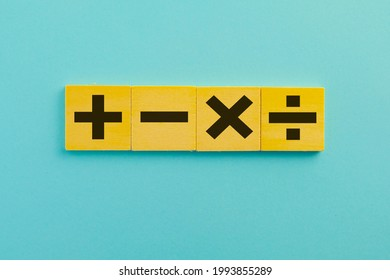 Black color of mathematical operations or Plus, minus, multiply, divide symbols on wooden cube over blue sky background use for mathematic,education,background,school concept.