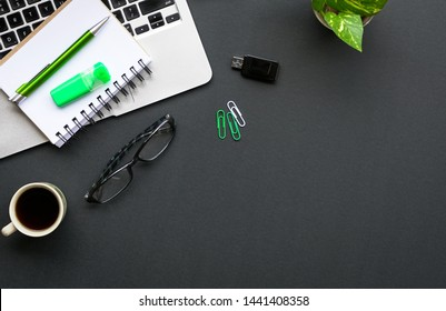 Black color office desk or table with laptop, coffee and other stationery, gadget with copy space. Top view or flat lay