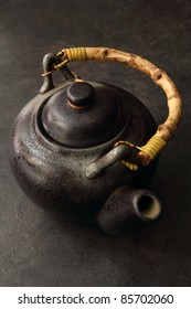 Black colored antique teapot with wooden rattan handle.
