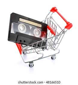 Black compact cassette with empty label in miniature shopping cart isolated on white background