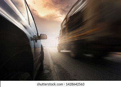 Black compact SUV car and blurry truck at full speed on the road with beautiful cloundscape.