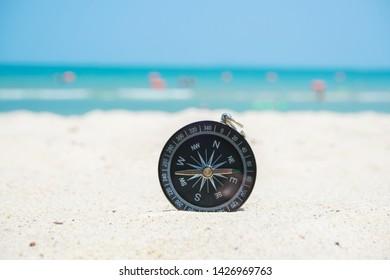 black compass on beach sand