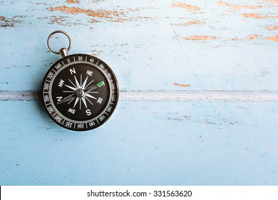 Black compass on wooden board