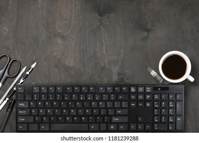 Black computer keyboard, cup of coffee and stationery on dark wooden table. Top view point of workplace.