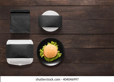 Black concept burger set on wooden background. Copy space for text.